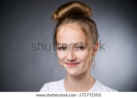 Portrait of a beautiful girl on a gray background in studio. - stock photo