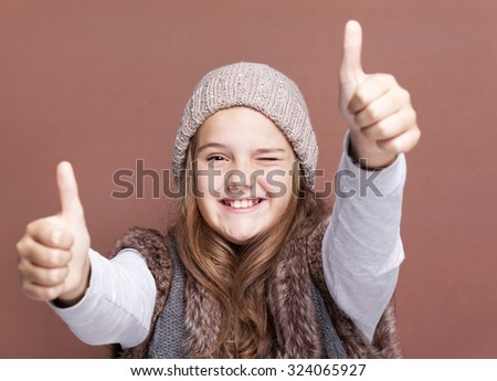 Portrait of a beautiful girl showing thumbs on brown background - stock photo