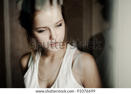 portrait of a beautiful girl through the window - stock photo