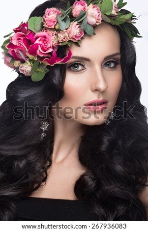 Portrait of a beautiful girl with a gentle make-up and lots of flowers in her hair. Spring image. Beauty face. Picture taken in the studio on a white background. - stock photo