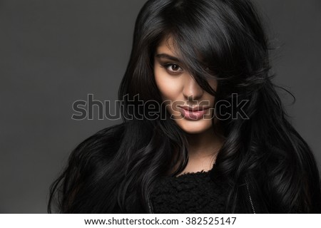 Portrait of a beautiful girl with black hair on a dark background - stock photo