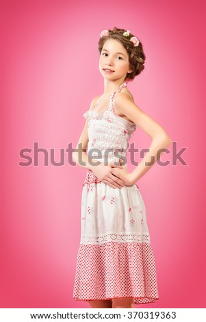 Portrait of a beautiful girl with braided hair wearing summer sundress. Children fashion.  - stock photo
