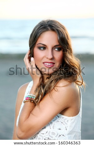Portrait of a beautiful girl with brown hair who is posing over a sky background - stock photo