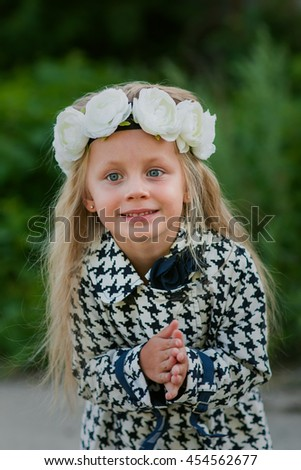 portrait of a beautiful girl with long blond hair and a wreath of white flowers on her head - stock photo