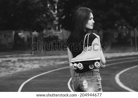 Portrait of a beautiful girl with roller skates on her shoulder walking down the street - stock photo