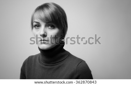 Portrait of a Beautiful  girl with sad eyes on a grey background. Beautiful sad girl with big blue eyes looking into the camera - stock photo