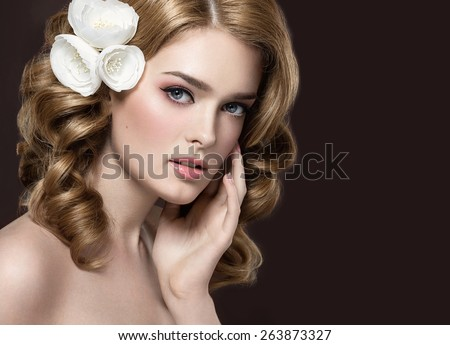 Portrait of a beautiful girl with white flowers on her hair. Beauty face. Photo shot in the Studio on a black background - stock photo