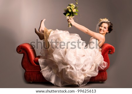 Portrait of a beautiful happy bride on red sofa in studio - stock photo