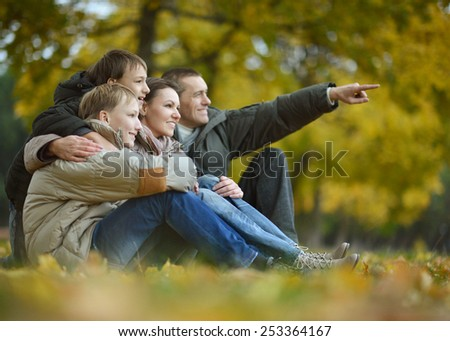 Portrait of a beautiful happy family sitting in autumn park,man showing something by hand - stock photo