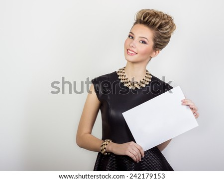 portrait of a beautiful happy sexy young woman smiling in a black evening dress with hair and make-up with expensive jewelry with a white sign in his hands in Studio on white background - stock photo