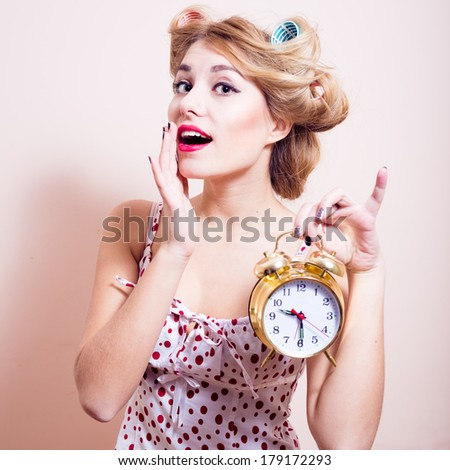 portrait of a beautiful happy smiling young woman looking at camera & showing alarm clock - stock photo