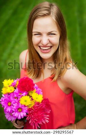 Portrait of a beautiful happy teenage high school senior girl holding a bouquet of flowers - stock photo