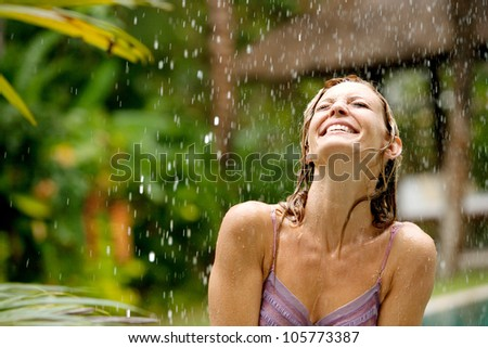Portrait of a beautiful happy woman enjoying tropical rain falling on her in an exotic garden. - stock photo