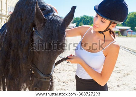 Portrait of a beautiful horsewoman wearing an equestrian helmet and a white top standing near a big brown horse, looking at the animal  - stock photo