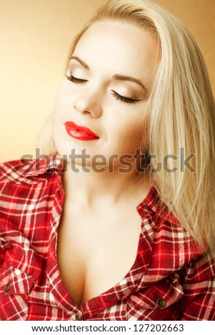 Portrait of a beautiful housewife (girl next door) with long blond hair in red casual shirt posing over wooden background. Close up. Studio shot - stock photo