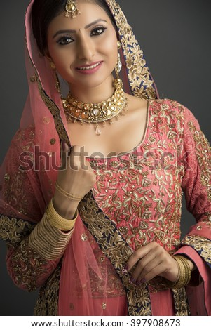 Portrait of a beautiful Indian woman in glamorous outfit and jewelry with makeup on dark background. - stock photo