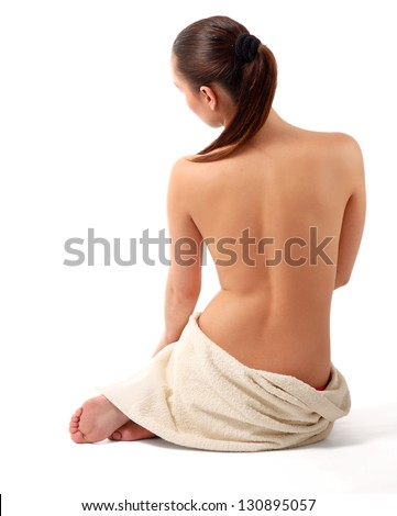Portrait of a beautiful lady covering herself with a white towel, isolated on white - stock photo