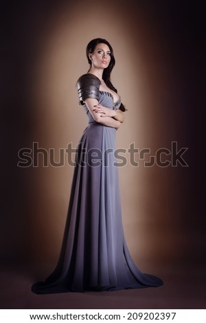 portrait of a beautiful lady warrior, dark-haired girl in a gray dress. bright makeup, hairstyle, spikes - stock photo
