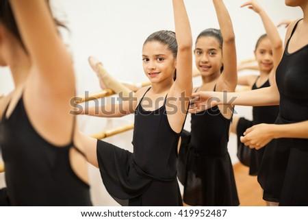 Portrait of a beautiful Latin girl enjoying her dance class among other girls and her teacher - stock photo