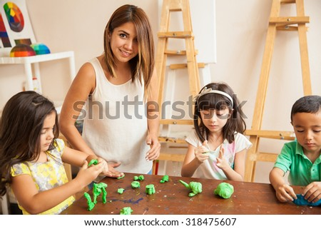 Portrait of a beautiful Latin teacher and her students working with clay during sculpting class - stock photo