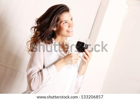 Portrait of a beautiful, latin Woman drinking red wine. - stock photo
