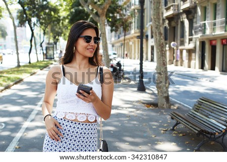 Portrait of a beautiful Latin woman with trendy look using cell telephone while walking outside in summer day, smiling attractive female chatting on her mobile phone during strolling in the fresh air  - stock photo
