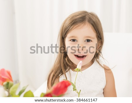Portrait of a beautiful little girl holding white rose flower looking at the camera smiling. Toddler girl giving flowers to her mom on mother's day - stock photo