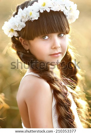 portrait of a beautiful little girl in a field - stock photo