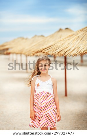 Portrait of a beautiful little girl in a sundress standing on a golden beach among tropical bamboo umbrellas - stock photo
