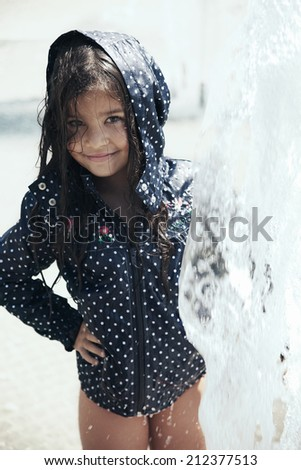 Portrait of a beautiful little girl playing in the fountain - stock photo