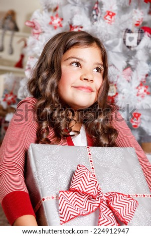 Portrait of a beautiful little girl with a Christmas present - stock photo
