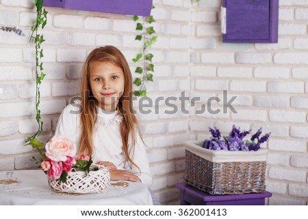 Portrait of a beautiful little girl with flowers sitting at the table. Little girl sits in front of a white brick wall in the studio. Textured brick background. - stock photo