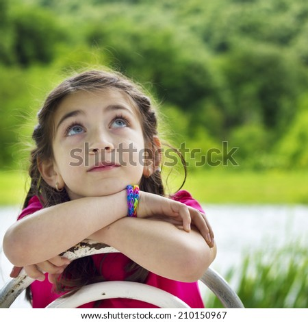 Portrait of a beautiful little girl with hands on chin looking up - stock photo