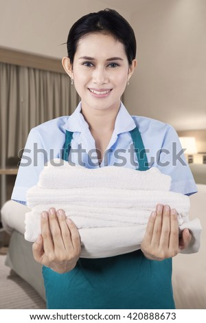 Portrait of a beautiful maid smiling at the camera while holding a pile of towels in the bedroom - stock photo