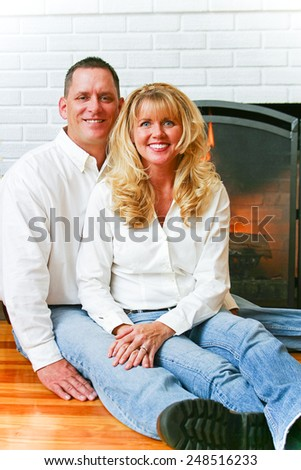 Portrait of a beautiful married couple at home in front of their fireplace.   - stock photo
