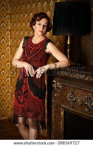 Portrait of a beautiful mature woman in evening dress standing in a room with classic style interior. - stock photo
