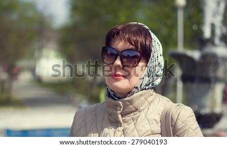 Portrait of a beautiful mature woman in sunglasses on a background of spring streets cape. - stock photo