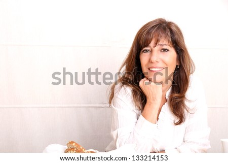 Portrait of a beautiful mature woman sitting in the kitchen. - stock photo