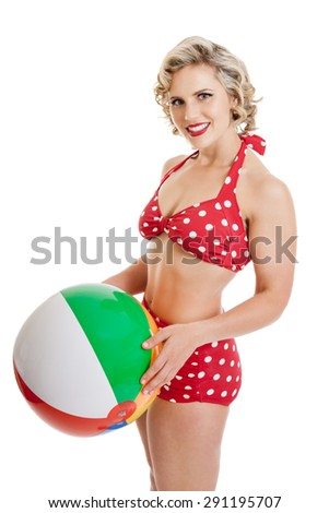 Portrait of a beautiful mid 30s woman dressed in vintage retro polka dot bikini holding beach ball isolated on white - stock photo
