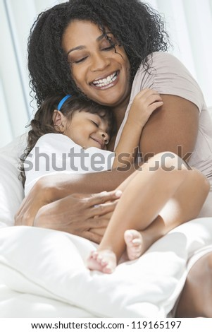 Portrait of a beautiful middle aged African American woman at home relaxing smiling laughing hugging her female child daughter - stock photo