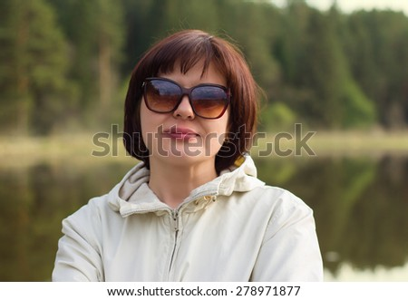 Portrait of a beautiful middle-aged woman in sunglasses, enjoying nature. - stock photo