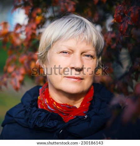 Portrait of a beautiful middle-aged woman outdoors. Color toned image. - stock photo