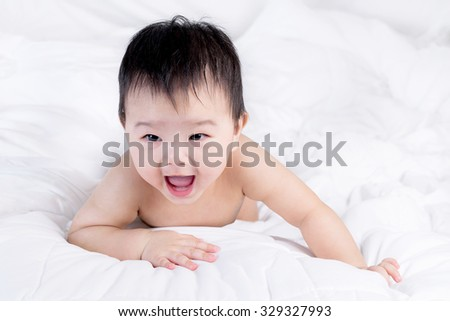 Portrait of a beautiful 6 months baby boy, cute baby lie on bed. - stock photo