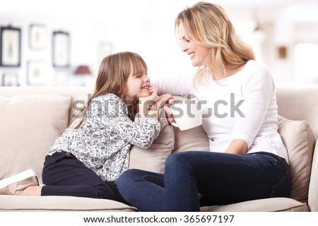 Portrait of a beautiful mother and her little girl sitting at home and sharing a happy moment together. Blond mom holding in her hand a cup of tea.  - stock photo