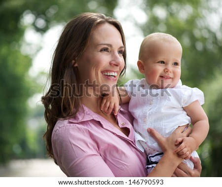 Portrait of a beautiful mother holding cute baby outdoors - stock photo