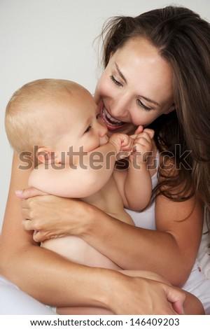 Portrait of a beautiful mother hugging baby laughing together - stock photo