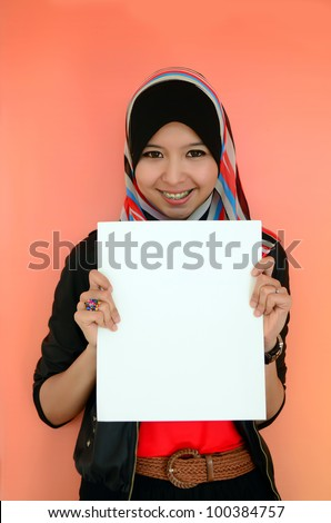 Portrait of a beautiful Muslim woman holding a white paper with smile, isolated on orange background - stock photo