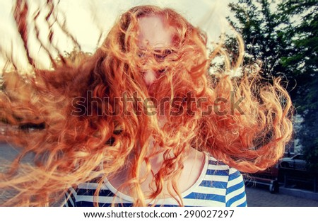Portrait of a beautiful redhead girl with flying hair in the wind outdoors. Young casual girl with wavy hair - stock photo