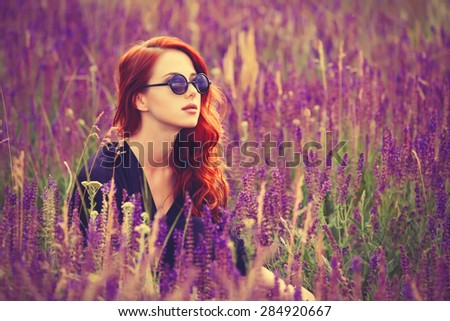 Portrait of a beautiful redhead girl with sunglasses on lavender field. - stock photo