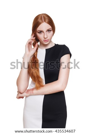 Portrait of a beautiful redhead woman in elegant black and white dress. Beauty, fashion model isolated at white. Young seductive lady with long hair. Opposites, contrast, day and night concept. - stock photo
